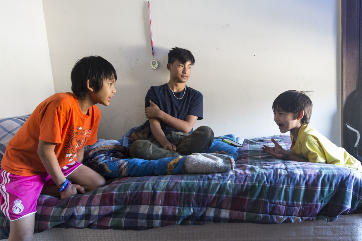 "Ehlerh Htoo, 17, sits on his bed while He Say Gay Htoo (left), 13, and He Say Wah Htoo (right) yell at each other. Ehlerh often takes care of his siblings, but says more often than not ""they talk too much."" April 18, 2015."