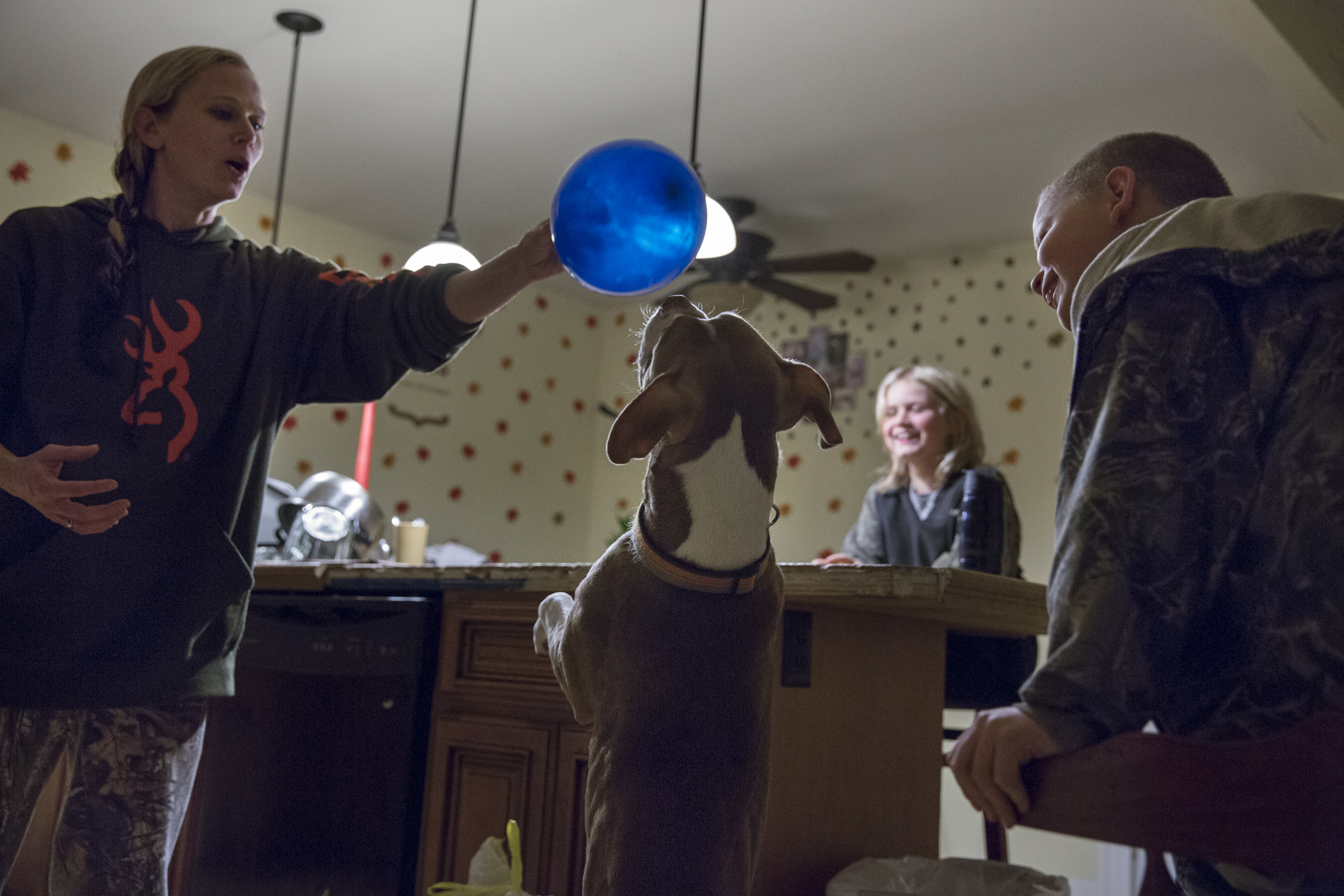 "Bridgette holds a birthday balloon out of the reach of ""Chevy"", the family dog, while Destinee and Layne laugh. The family spends a lot of time together in close quarters and find creative ways to have fun. Nov. 24, 2014."