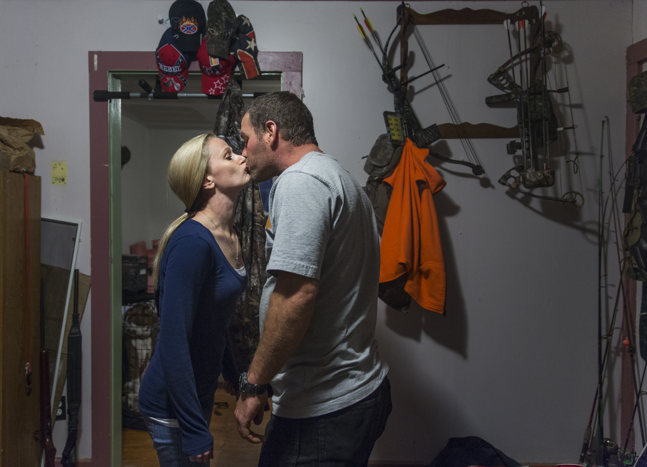 Bridgette and Luke kiss in their smoking room before returning to their kids' birthday party. Luke stores all of his hunting, fishing, and trapping equipment in the room that he and Bridgette smoke cigarettes in. Nov. 23, 2014.
