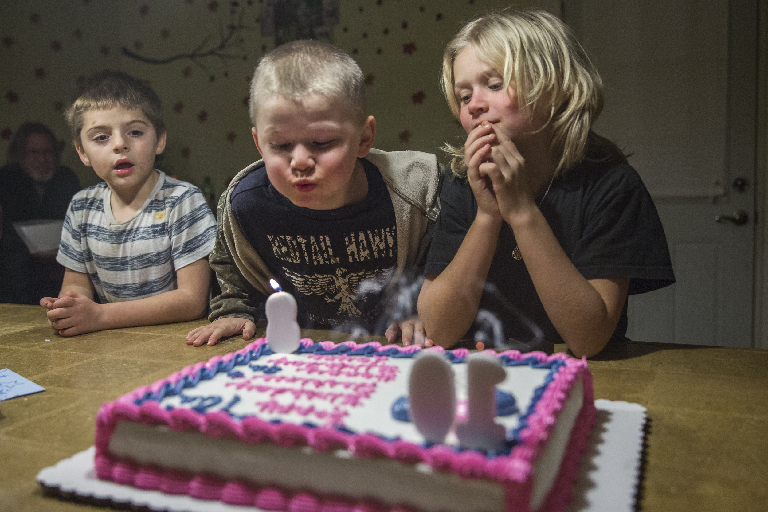 "(Left) Ronnie Bauer, 6, and Destinee (right) watch as Layne blows out his birthday candle at their combined birthday party. Destinee and Layne ""fight like cats and dogs at home"", says Bridgette, ""but when we're not around, she watches him like a hawk."" Nov. 24, 2014."