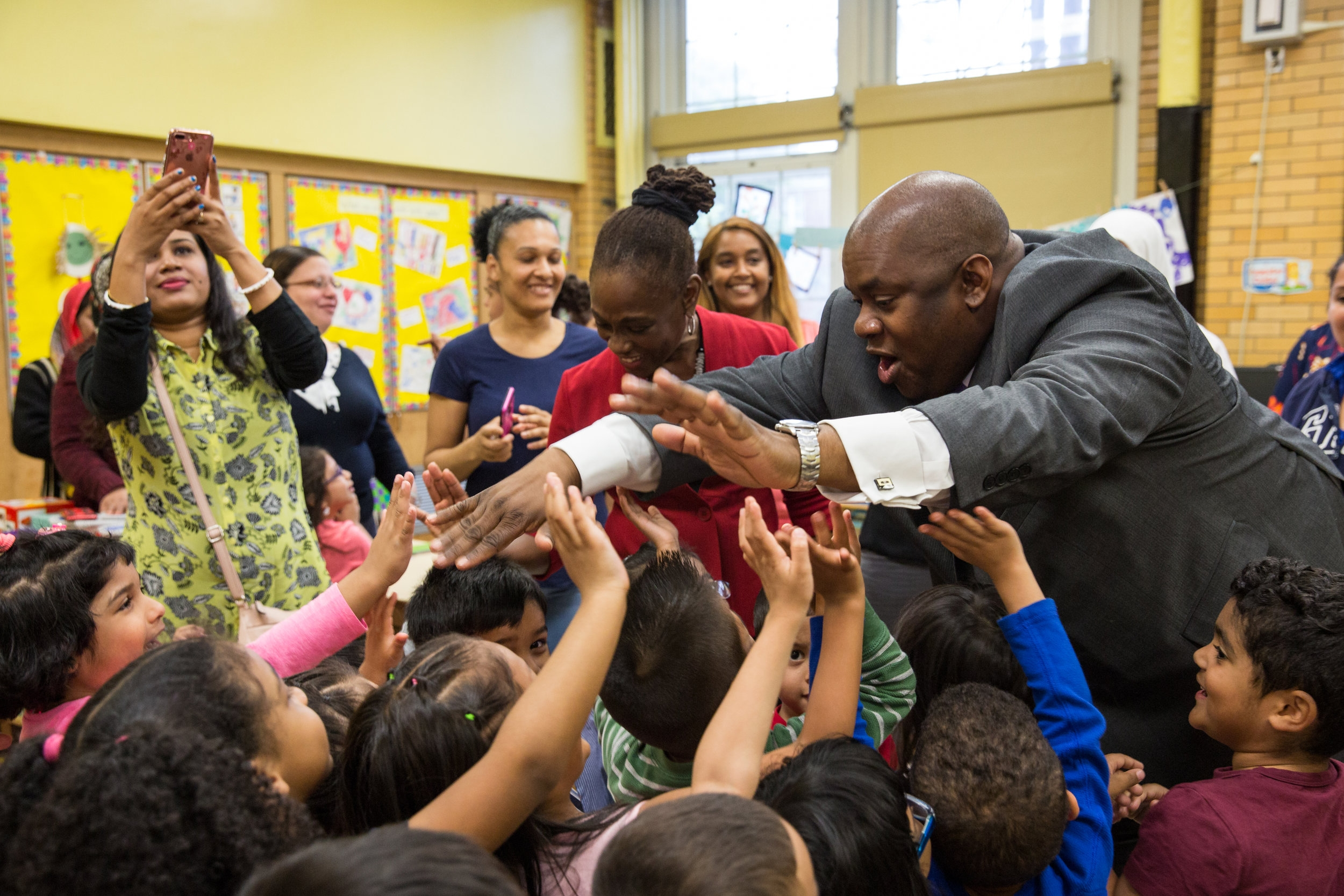 """New York City First Lady Chirlane McCray and Deputy Mayor Richard Buery high-five a Pre-K class at P.S. 119 in the Bronx on May 25, 2017. The First Lady and Deputy Mayor visited the class to play """"Fun with Feelings,"""" a card game that teaches emotional intelligence.( For   New York City Mayor's Office)"""