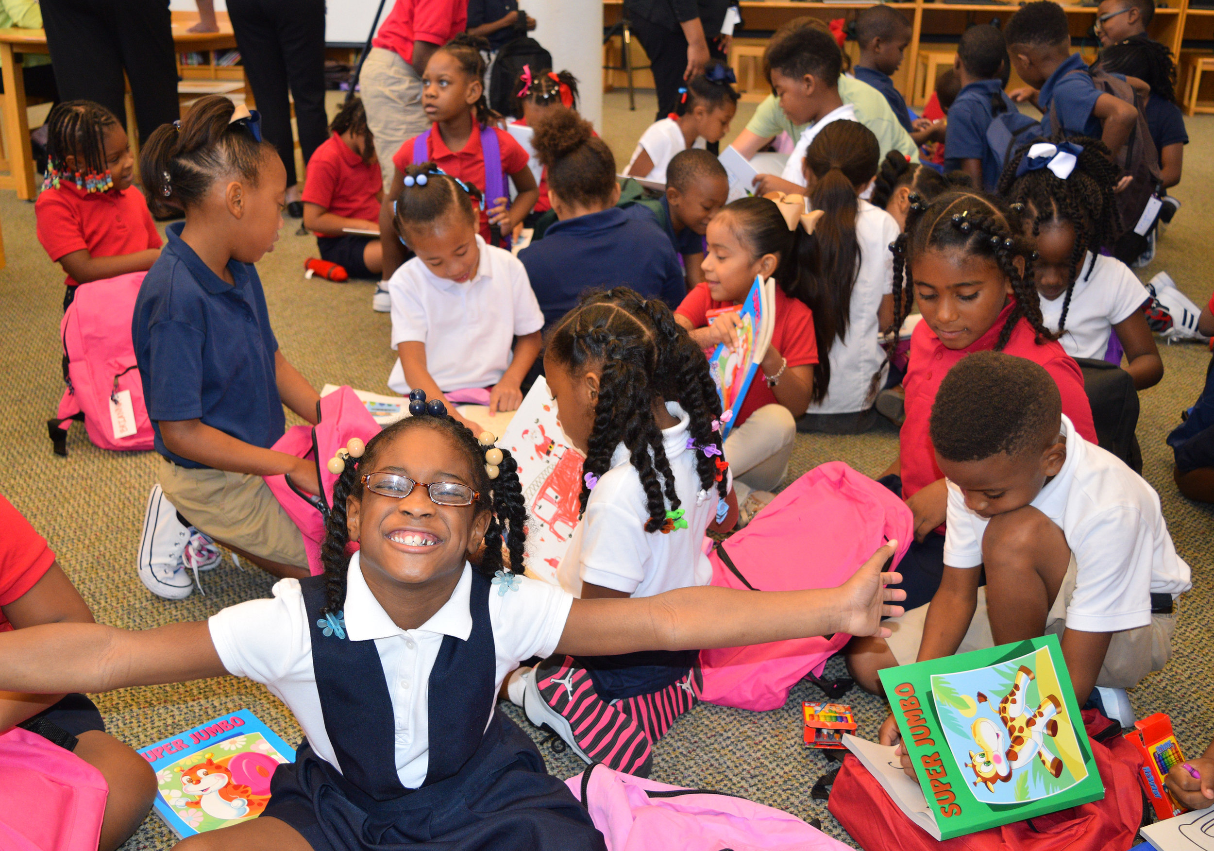 Students at Foster Elementary in HISD enjoying their new books and backpacks