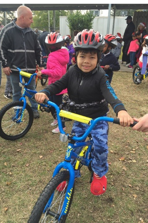 Neff ECC student rides off with a new bike he earned by meeting reading goals.