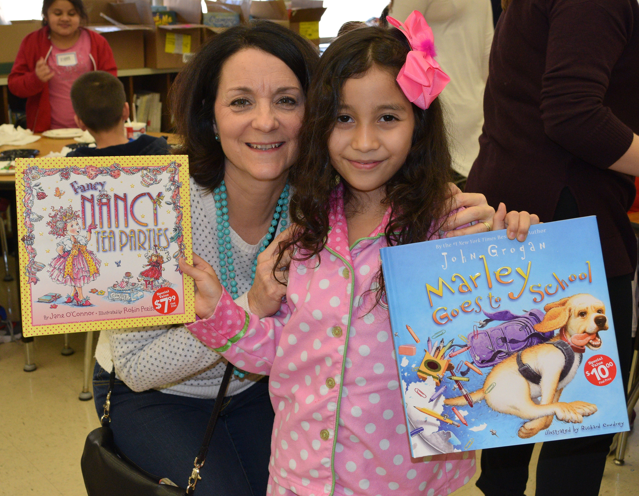 Making It Better Executive Director Jacque Daughtry with student at Ross Elementary School holding new books donated by Scholastic Book Fairs®.