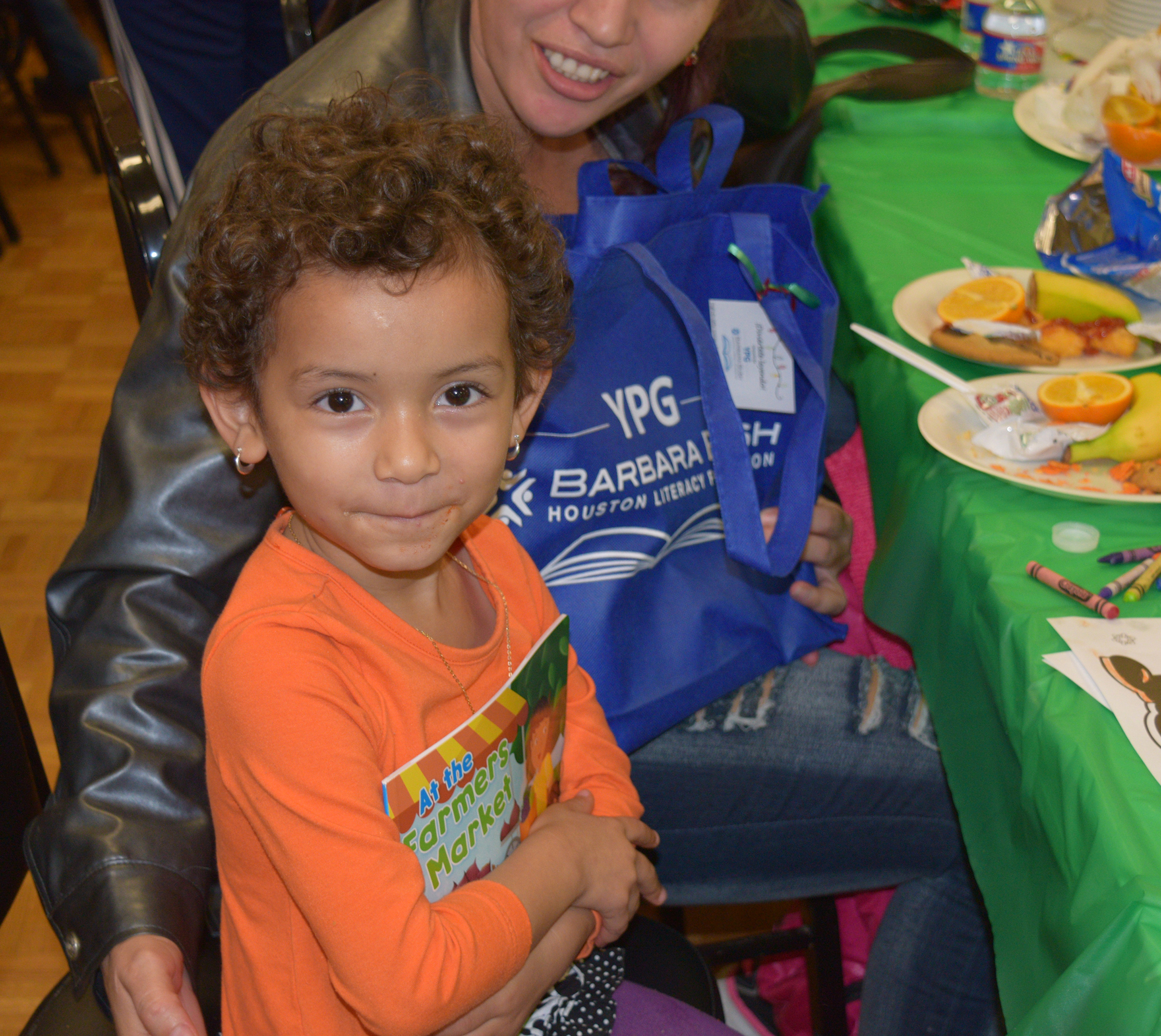 Child hugs book distributed by our Young Professionals Group at the annual Kids' Meals, Inc. holiday celebration.