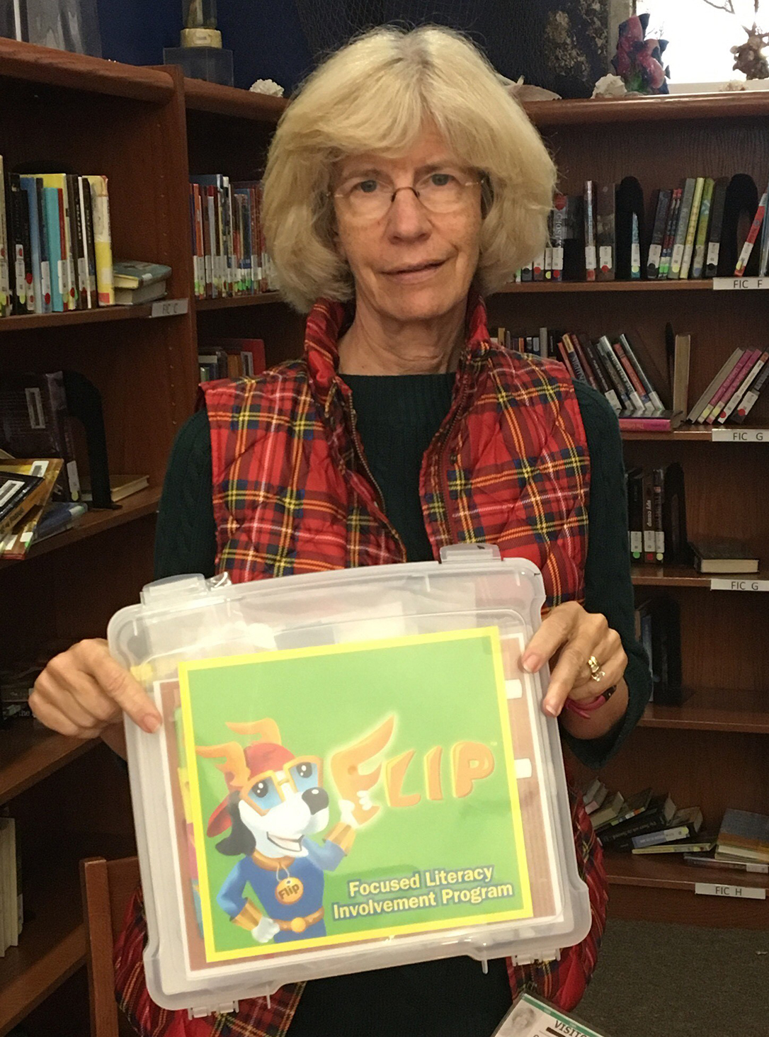 "Catherine Geis holds a Focused Literacy Involvement Program (""FLIP"") kit that she uses during her 30-minute reading sessions with a child."