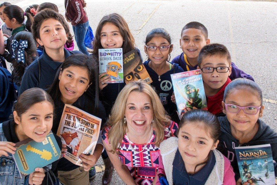 Dr. Finck stands with a few of the 560 children sponsored through My Home Library in March.