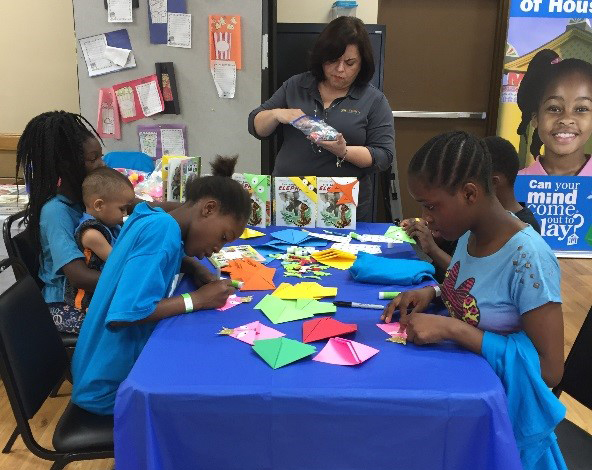 Legacy Community Health's Maria Cantu works with children at one of the many creation stations.
