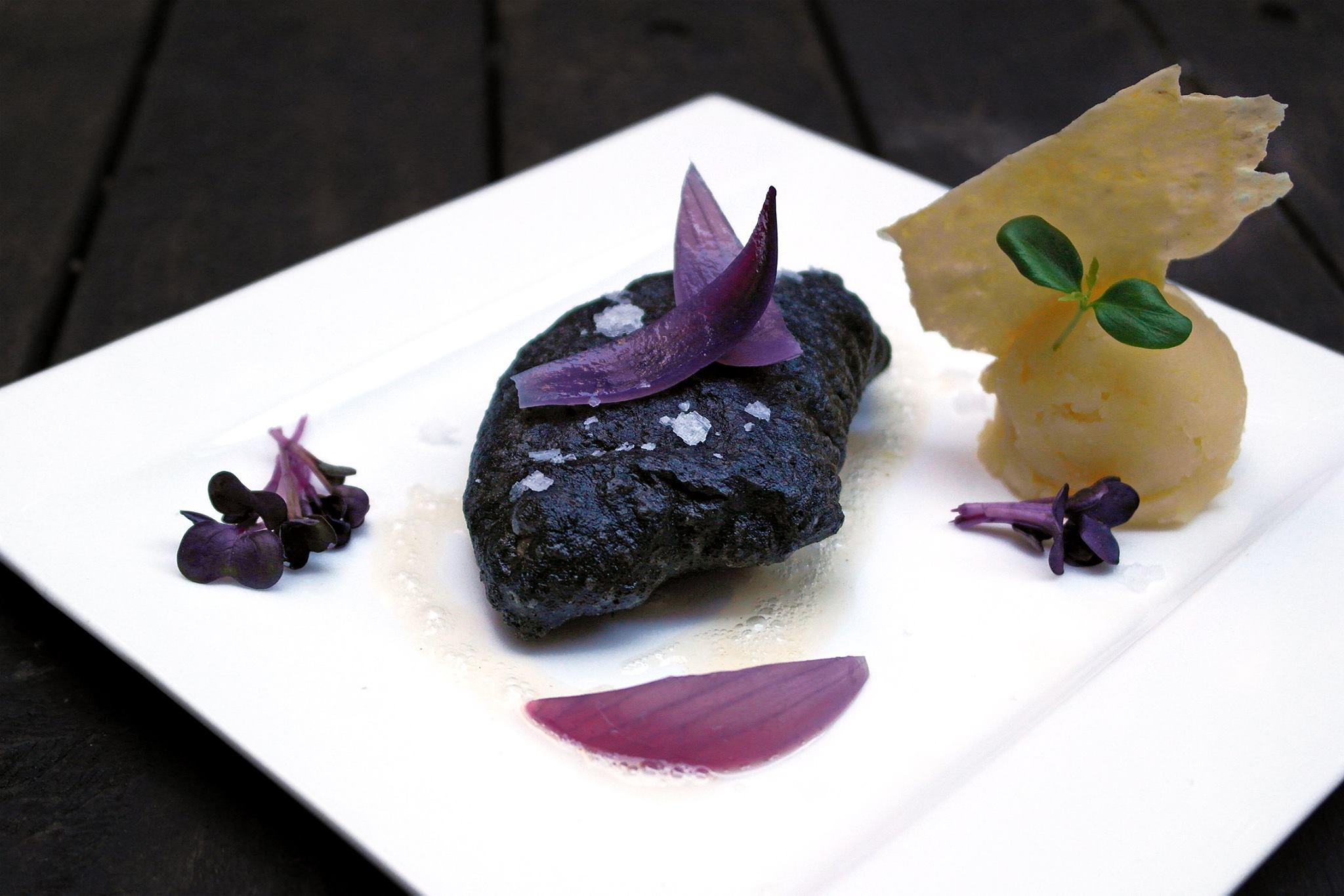 Filetto di salmerino alpino in pastella di carbone, sambuco e prosecco, patate alla vaniglia e cipolla rossa al forno. Facebook/Il Chiostro di Andrea