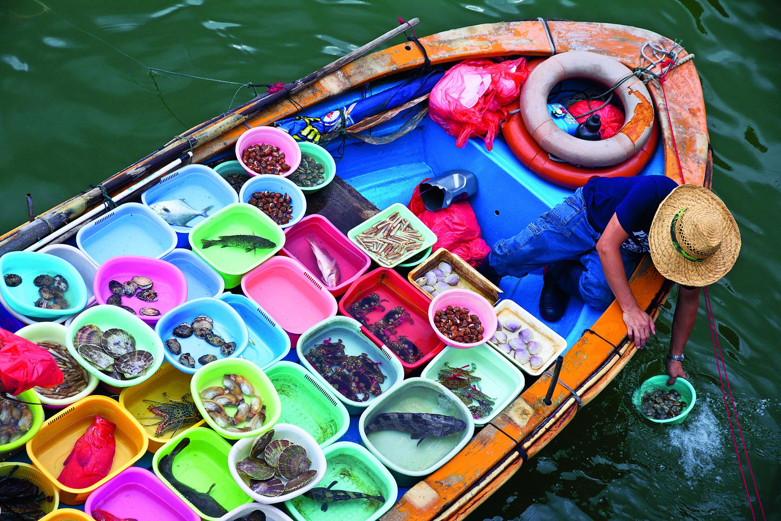 Un nuovo volume enciclopedico e autorevole mette in mostra la diversità culinaria della cucina cinese con ricette provenienti dalle 33 regioni e sottoregioni della Cina. Nella foto un pescatore vende frutti di mare sul suo sampan, una piccola imbarcazione tipica di quelle zone, al molo di Saikung.