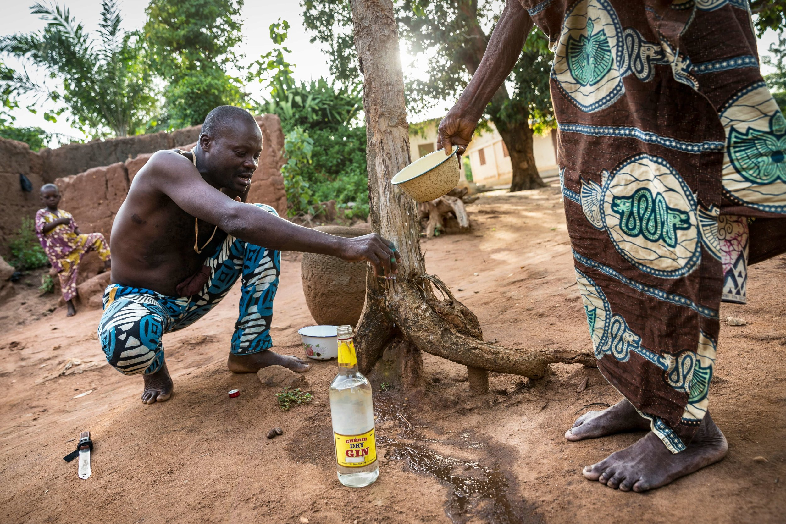 The chef-du-village opening the Revenant Voodoo celebration pouring gin and making offers at the tree of the ancestors.