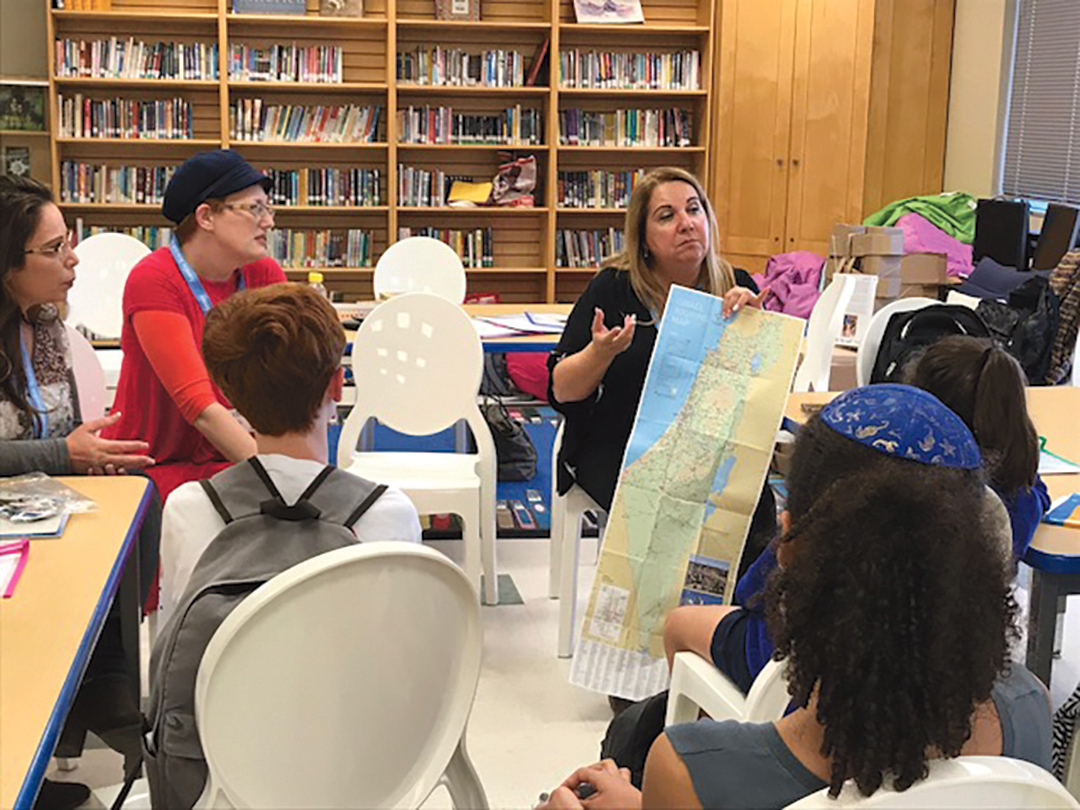 Students at Congregation Agudas Achim Religious School study a map of Israel with Partnership2gether visiting educators. (Shelly Prant)