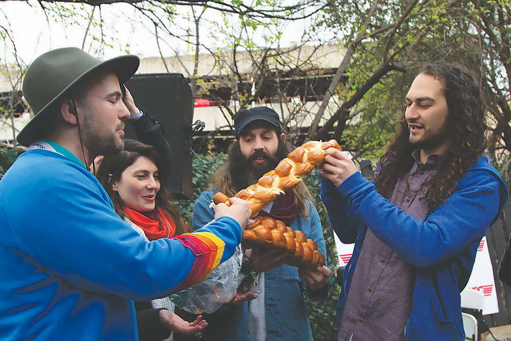 Kosha Dillz, JonZ and Adam Swig share challah with the crowd at Empire Shabbat March 15. Credit: Wendy Goodman