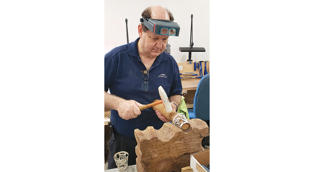 Finkel shaping his original crown design to replace missing parts for a pair of rimmonim (Torah decorations). Credit: David Finkel Photography.