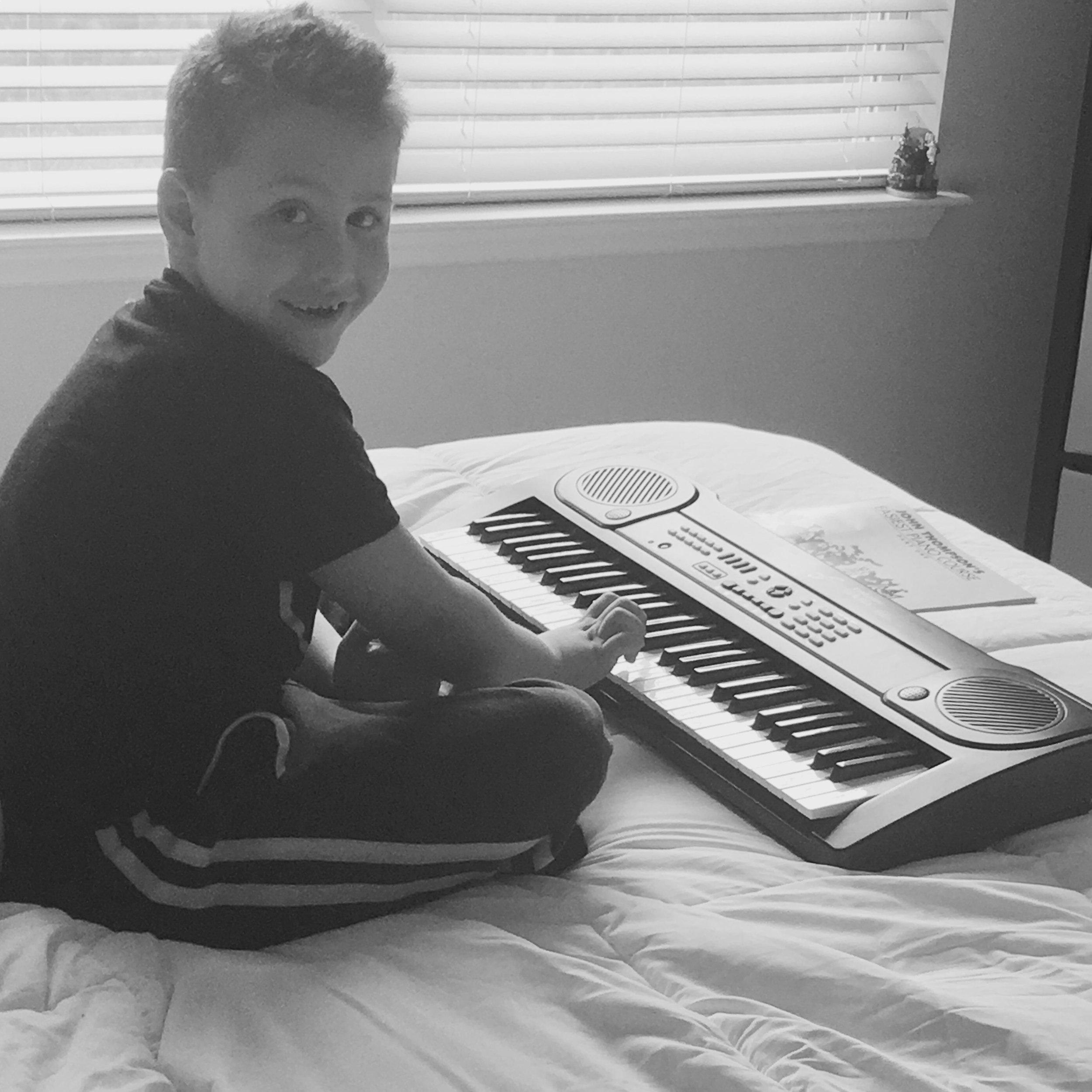 Music class consists of Momma teaching this boy how to play the piano.