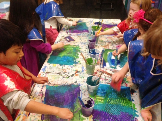 Children painting at a table together.