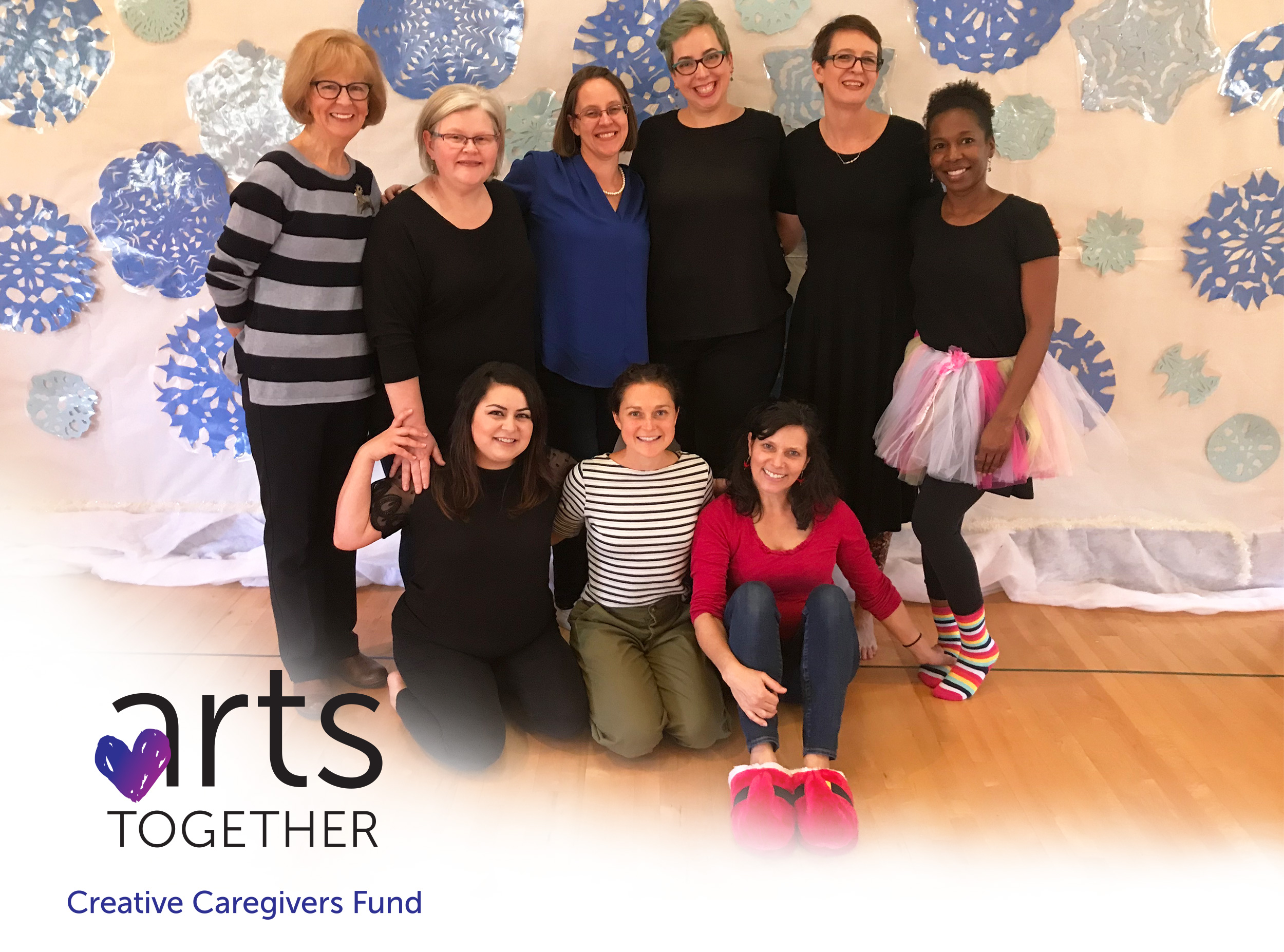 Arts Together's Preschool faculty members in a group shot, smiling. The Creative Caregivers Fund logo that features a purple heart is overlaid in the bottom left corner.