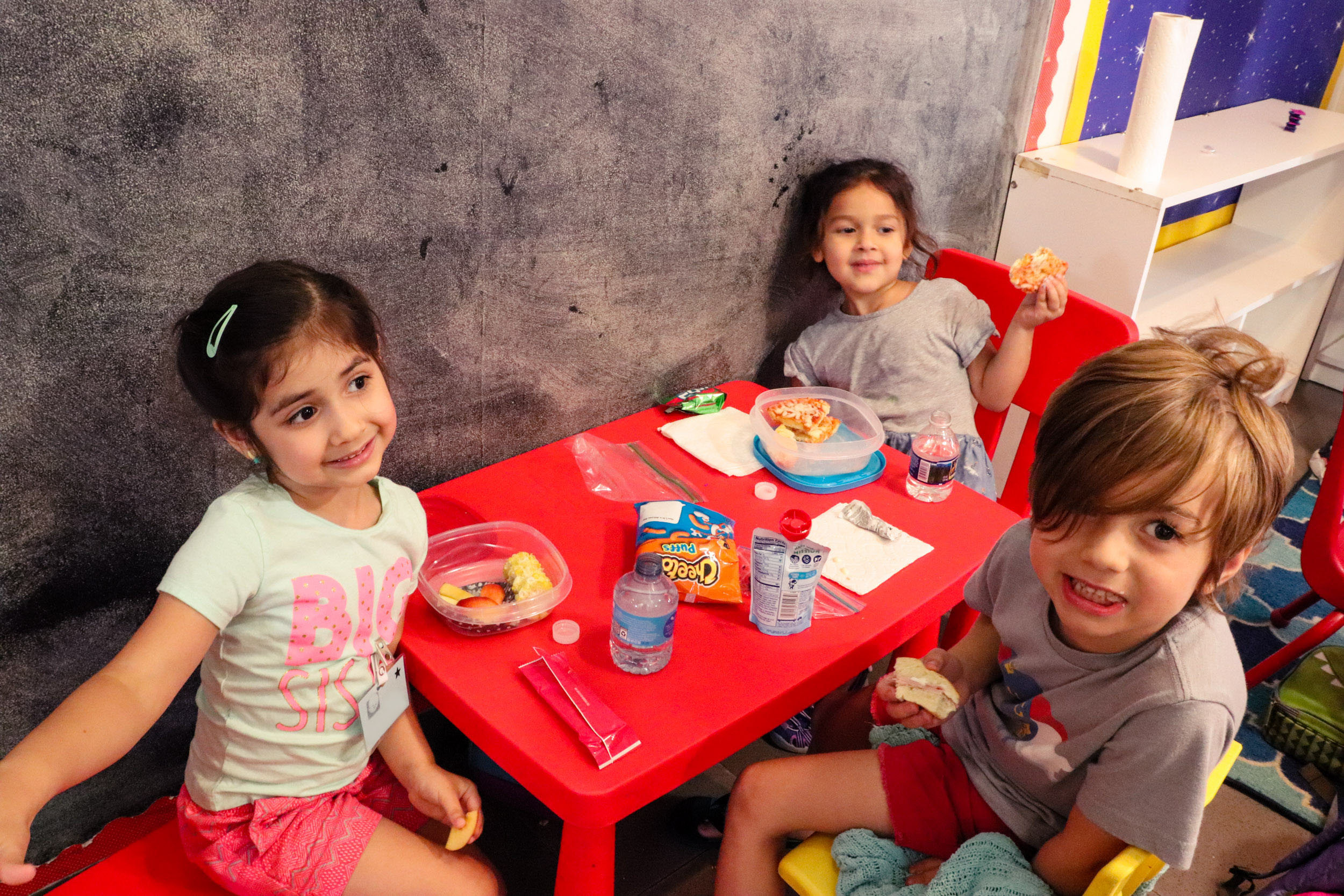 Three preschoolers eating lunch together around a red table, smiling.