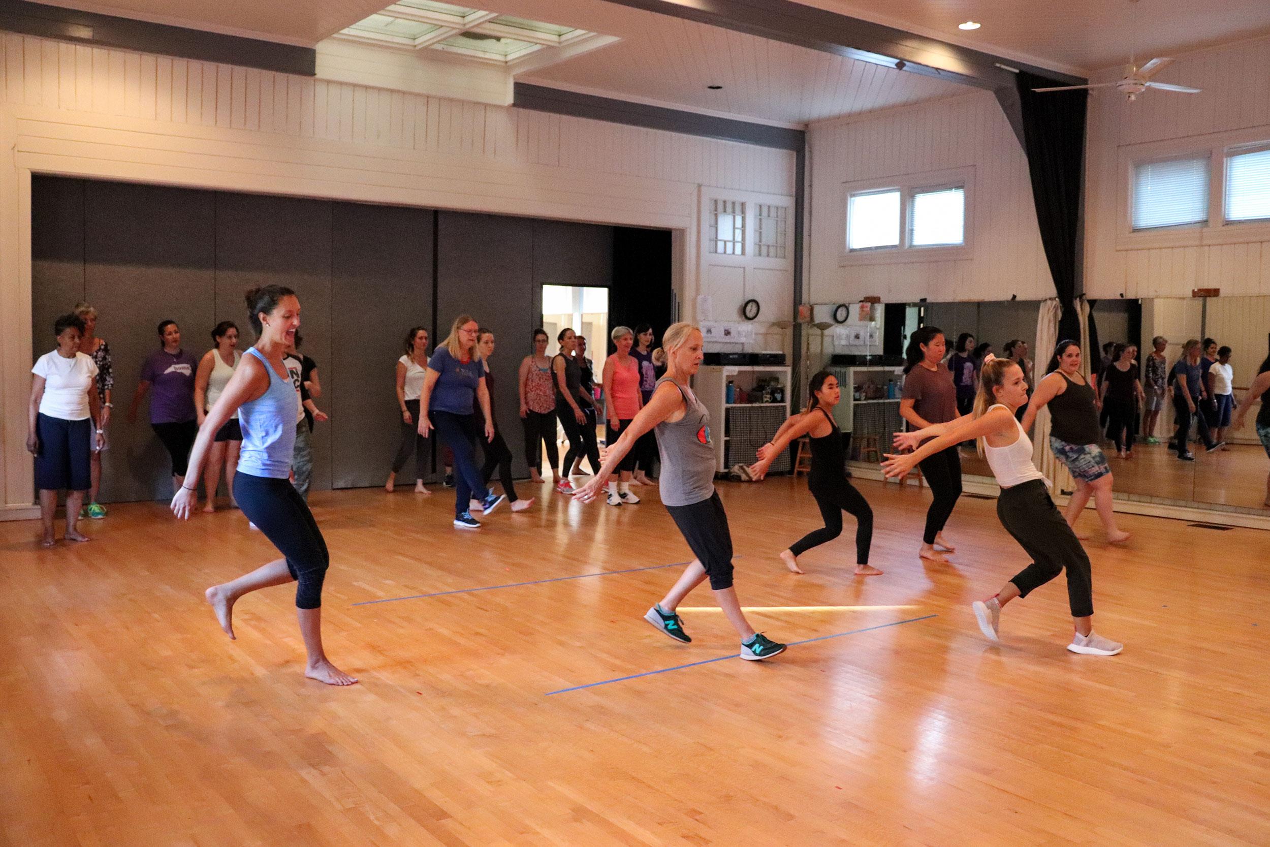 Adult students practice hip hop dance moves in a line across the dance floor.