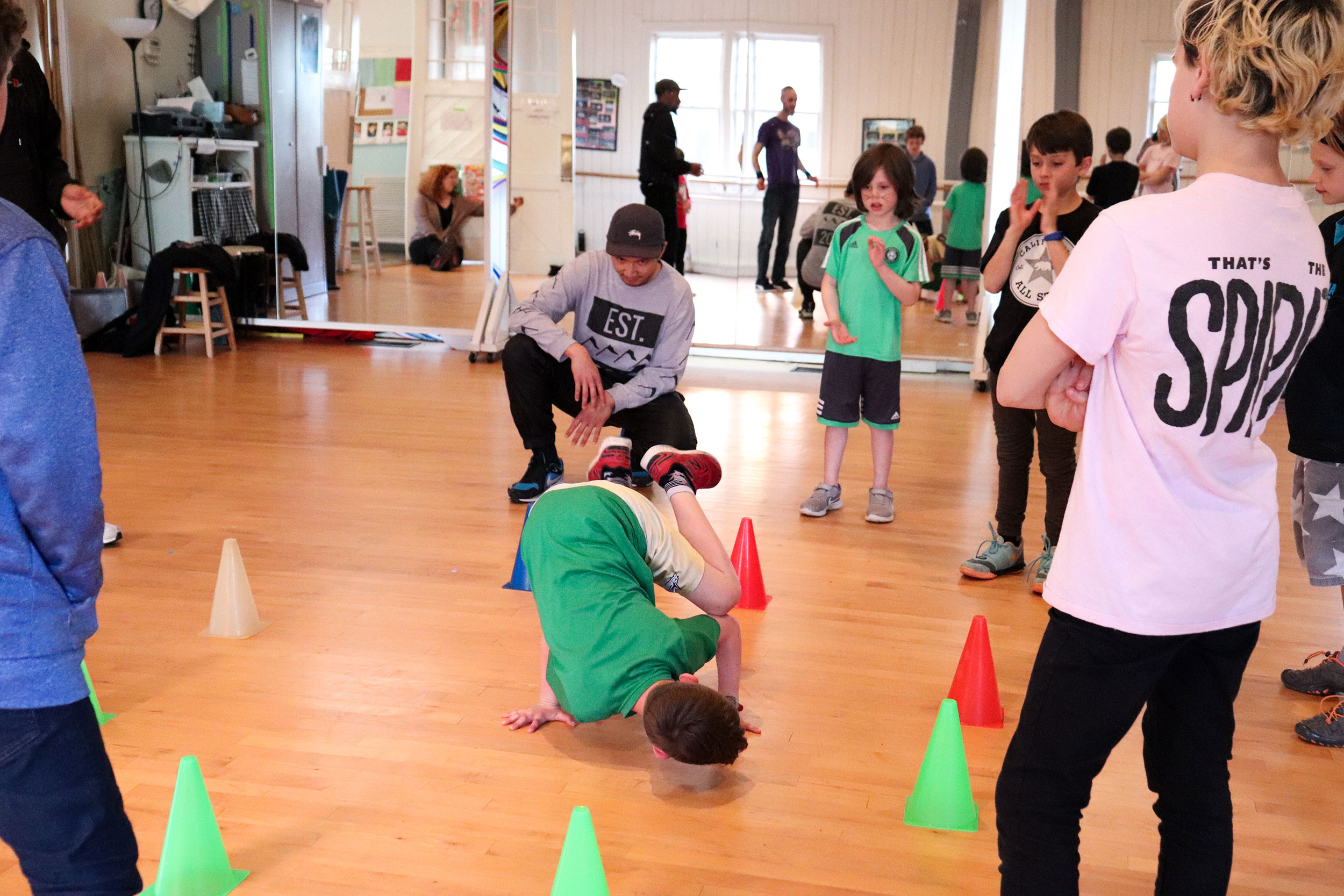 A child shows off his cool breakdancing move for the class.