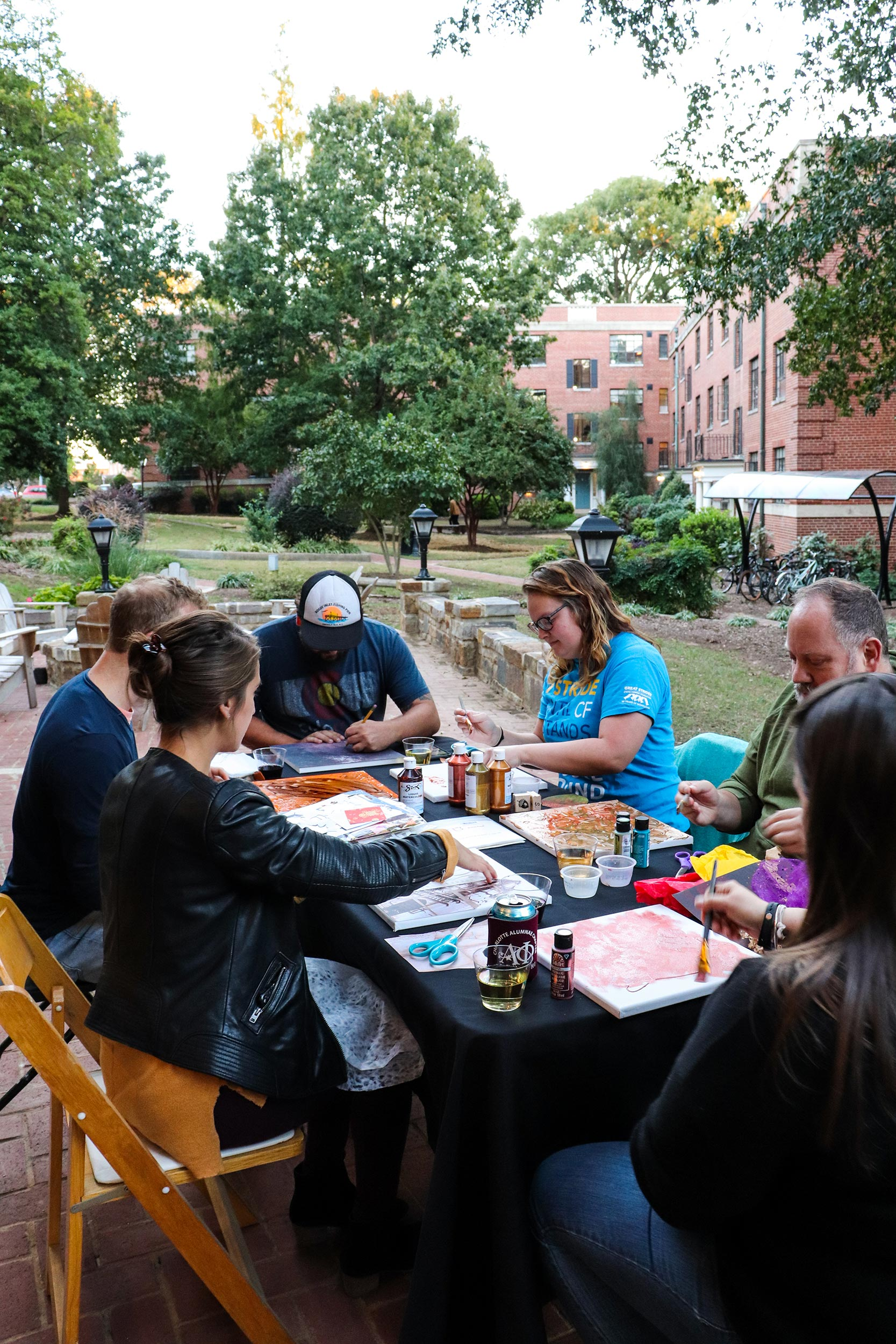 Adult art students get creative outdoors using paint and collage on canvas.