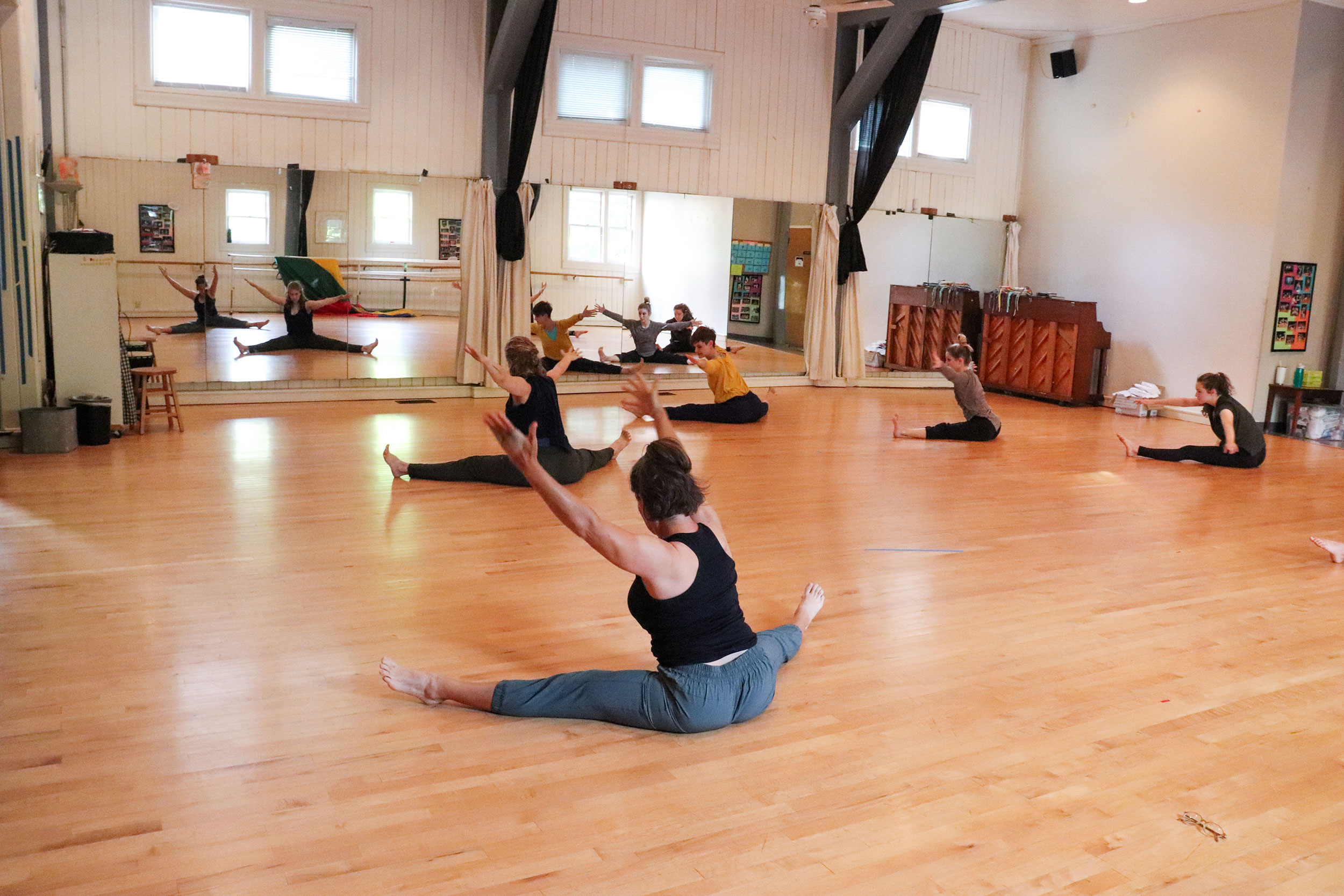Adult students learn modern dance movements.