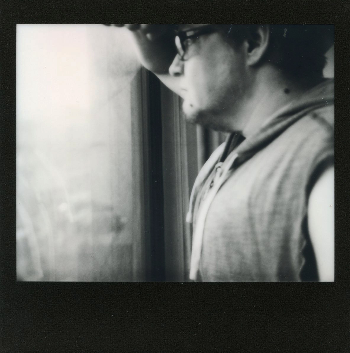 In this black-framed instant photo, a white man visible in profile from chest to forehead leans his arm against the pane of a large window. He wears glasses with thick rectangular frames and a lightweight gray hoodie with the sleeves torn off. He has a short, light-colored beard. The picture has a pensive, dreamy feel, and by a trick of the light it appears that the windowpane is bowing slightly toward the man where his arm rests against the glass. (The image is a self-portrait).