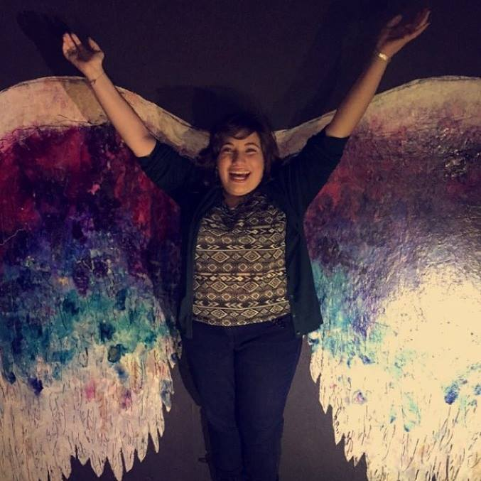 A young white woman with her arms raised. She is smiling and standing in front of a mural of wings painted various shades of pink, purple, blue, and white. She is wearing a green cardigan, jeans, and a T-shirt with triangular prints.