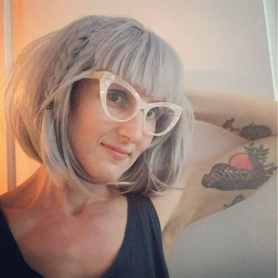 A photo: selfie of the artist Karrie Higgins. She is an adult white woman wearing glitter glasses & blue-gray bobbed hair. She poses with one hand behind her head, casually displaying the large falcon tattoo on her inner bicep. Her mysterious smirk is reminiscent of the Mona Lisa.