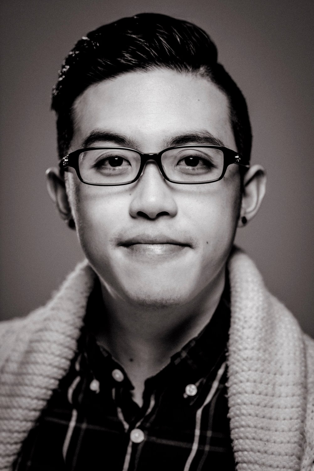 A black and white portrait with myself standing in a white knit cardigan and plaid shirt.