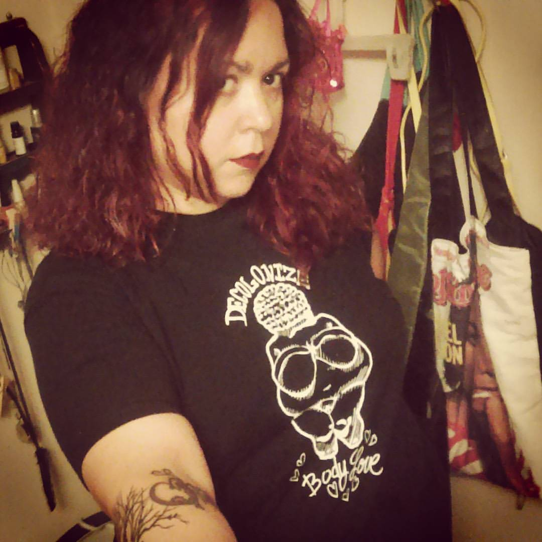 """A selfie taken by the poet, it shows the femme person, a Chicana/Boricua brown person, who is not smiling, with dark red & black curly shoulder length hair, wearing dark red lipstick and a black t-shirt that reads """"decolonize-body love"""" with an image of a fat femme person. Noemi's arm is tattooed with a heart and tree branches and her arm is outstretched, holding the camera."""