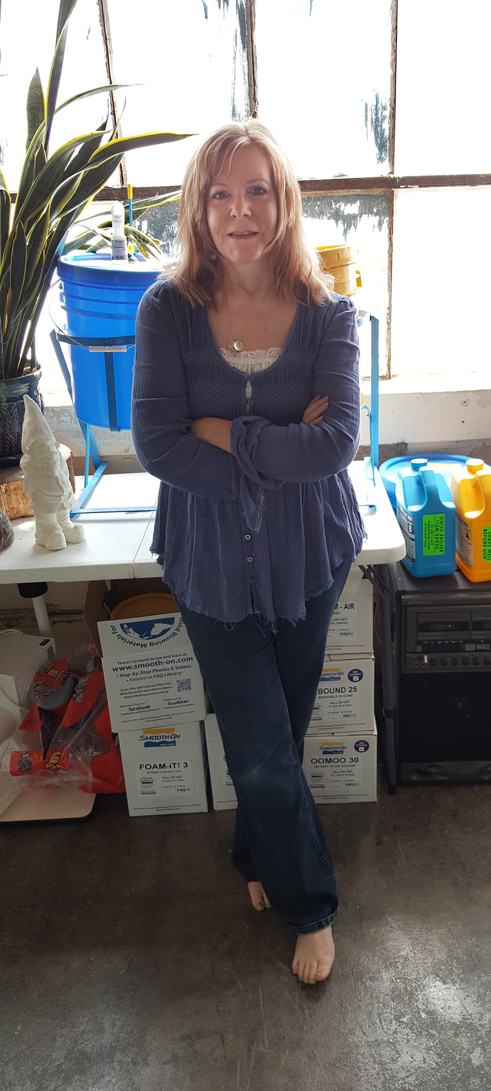 A white woman with medium-length red hair in jeans & a blue top leans against a table in a cluttered studio.