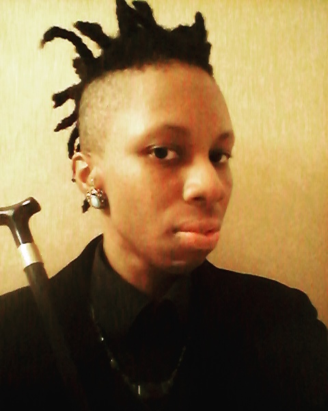 Lynx Sainte-Marie, a non-binary Black spoonie with loc'd hair and shaved sides, looks into the camera with a serious expression on their face. They are wearing a Black velvet blazer, a Black dress shirt, a dark statement necklace covered in stones and turquoise earrings with gold trimming. Their Black and gold cane can be seen partially in front of them, tilted to the left.