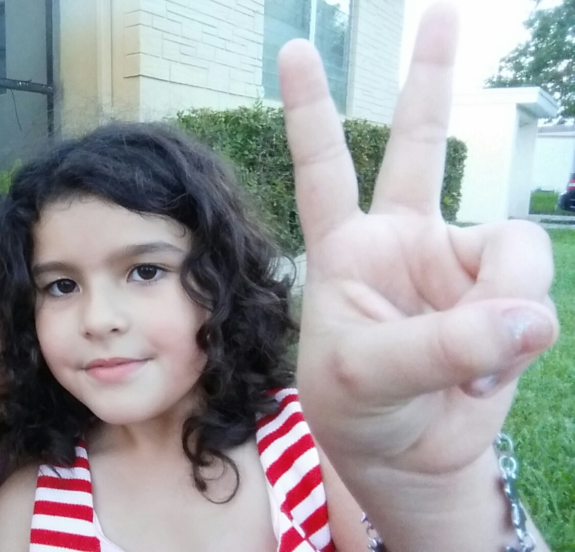 Color photograph of a the painter Nimue, a young curly-haired Chinese Jamaican Hispanic girl with a mysterious half-smile. She holds out her left hand in a peace/victory sign, and the camera foreshortening makes her hands huge.