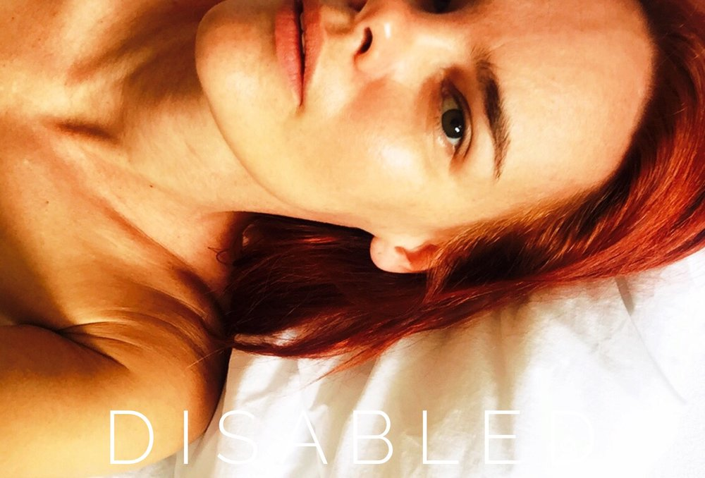 [Image Description:Erin lies on her back looking up at the camera. The image crops close, showing only the left half of her face and one shoulder. She has red hair and very dark eyes. Sans-serif font reads DISABLED.]