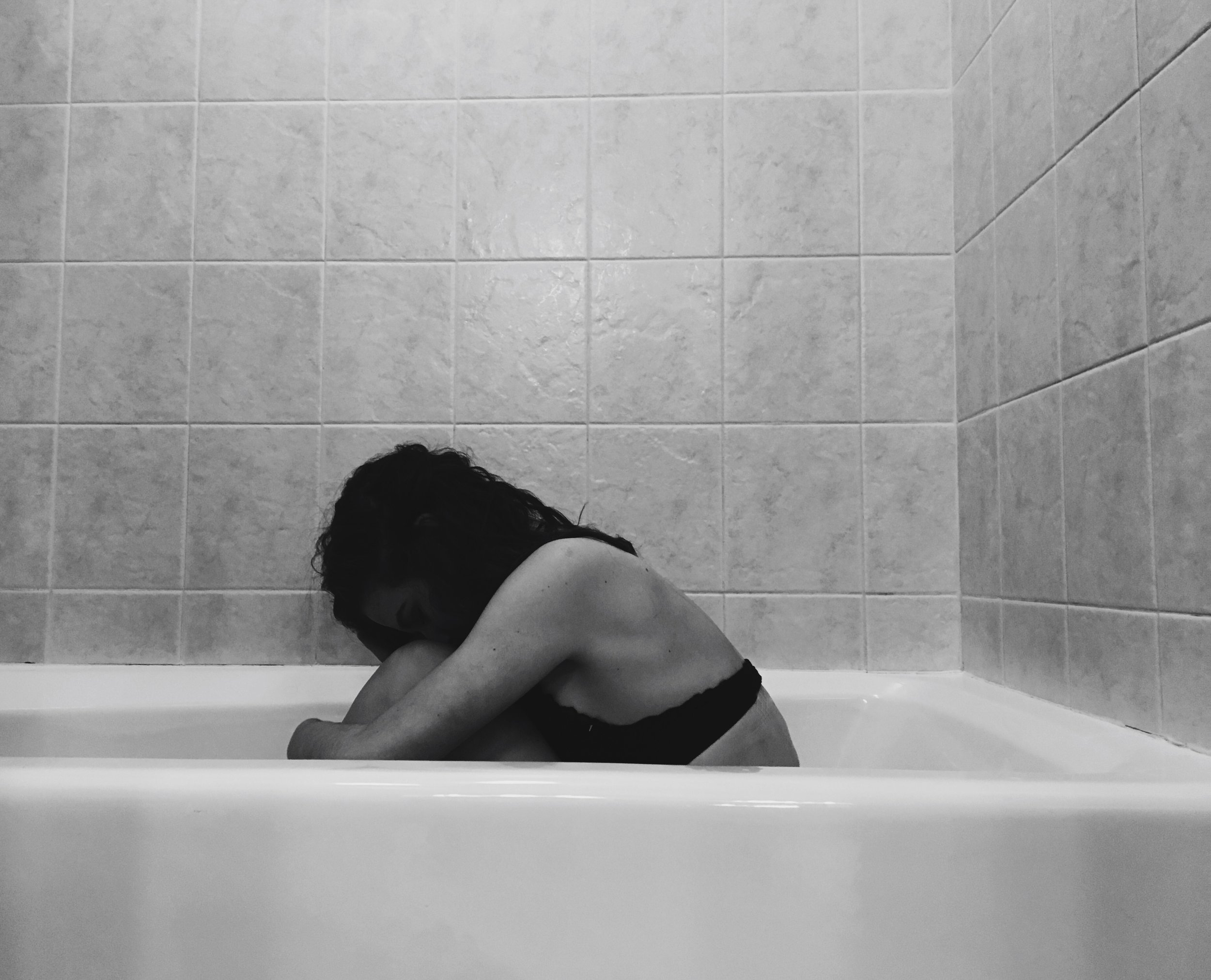 Photo by Kaitlyn Brennan (artist/model) /Sophie Perry (photographer).  [Image Description:The looming tiles and the width of the tub seem to dwarf her fragile body. She curls into herself, head on her knees, black bra digging into her visible ribs. How can she seem so small now?]