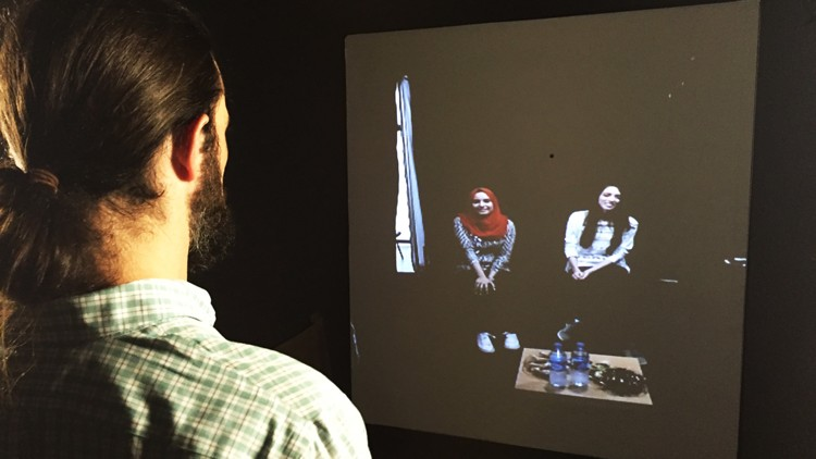 A virtual portal housed inside a shipping container allows visitors at St. Edward's University to communicating by videoconference with people all over the world. In this photo, Tony Chavez (left), who works at the university and was on the committee for the project with Shared Studios, speaks to Mona Safadi (center) and Amira Alami (right), students who attend college in Gaza.
