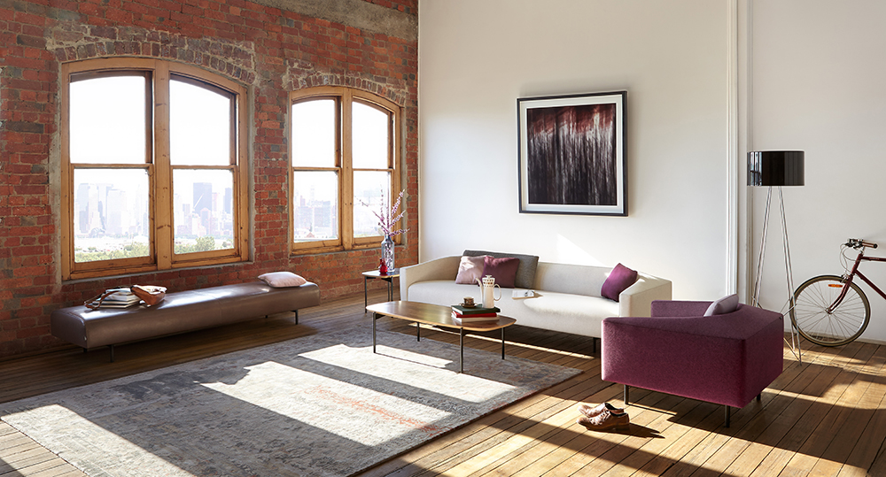 The furniture here is placed away from the rug to open the zone up, and make the most of the cavernous space