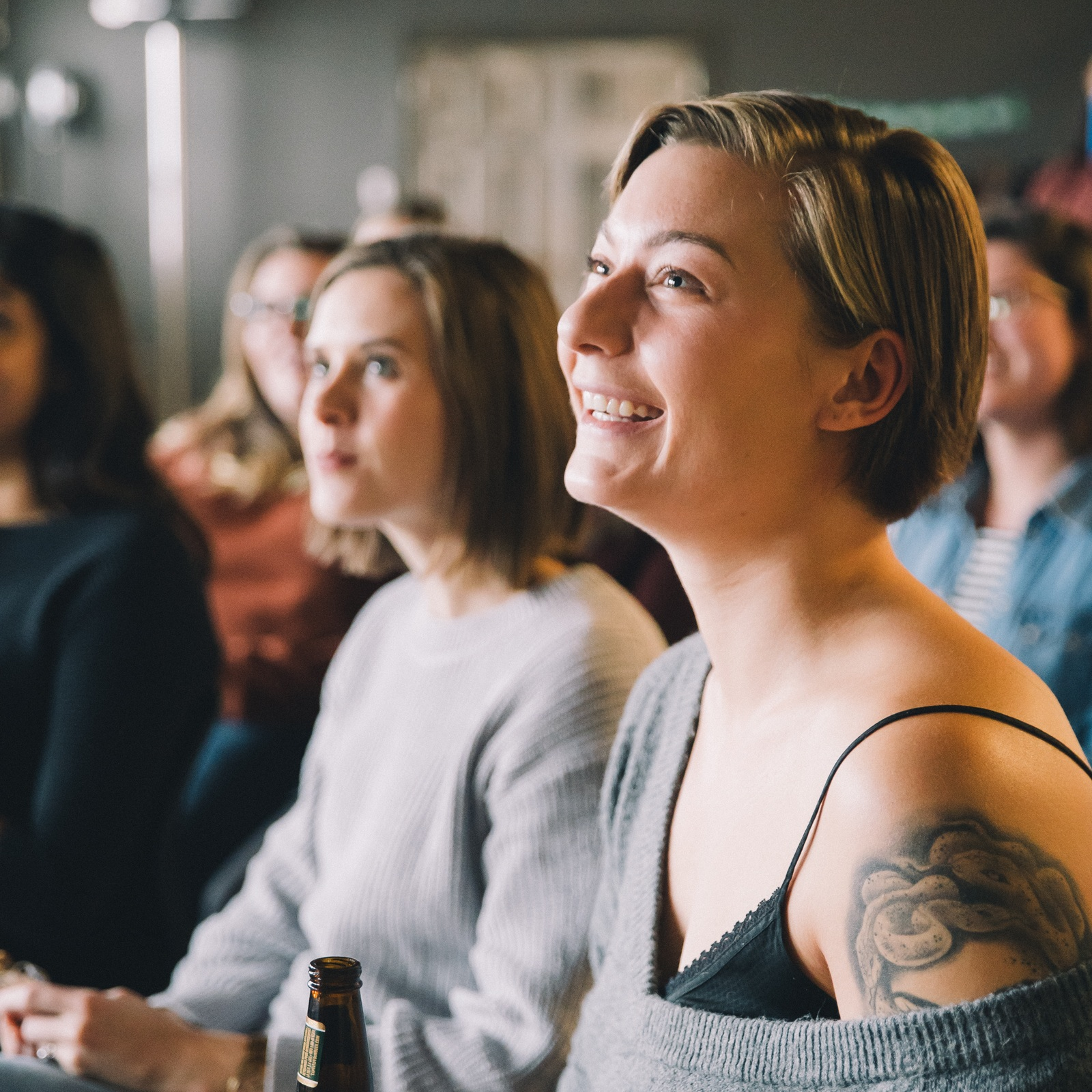 Woman smiling while sitting in audience at a Syzygy women's event.jpg