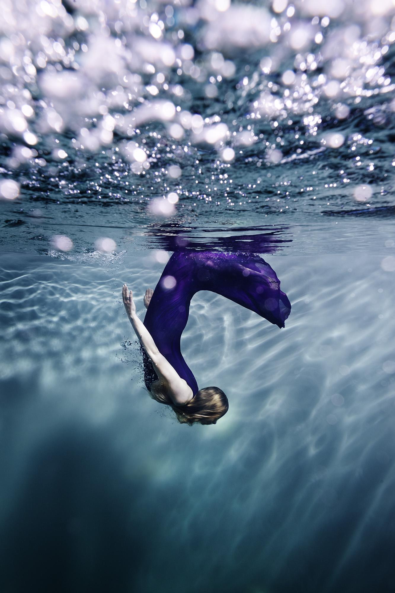 Susanne Stemmer girl doing flip in purple dress underwater