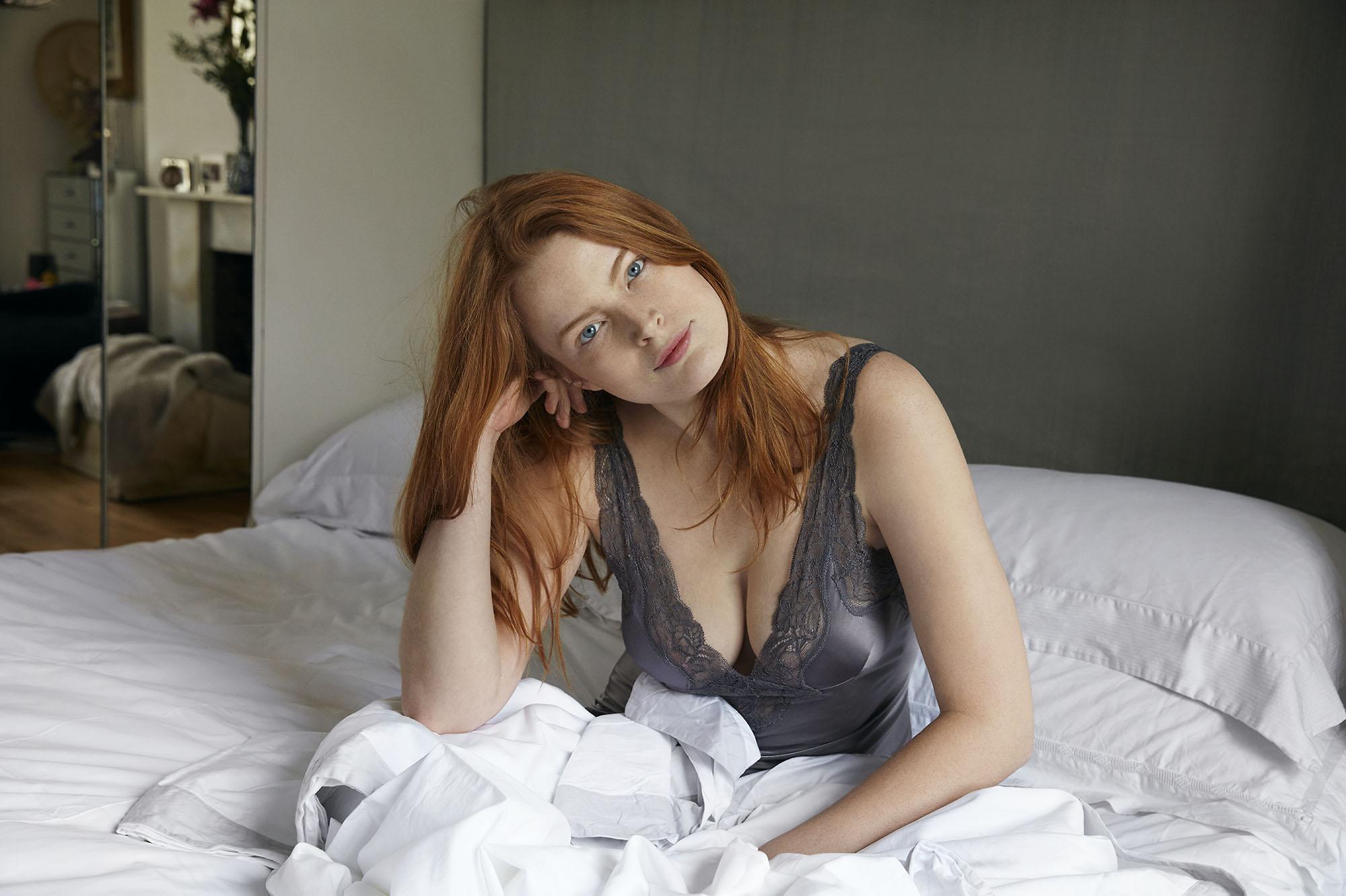Karan Kapoor red head girl sitting in bed.