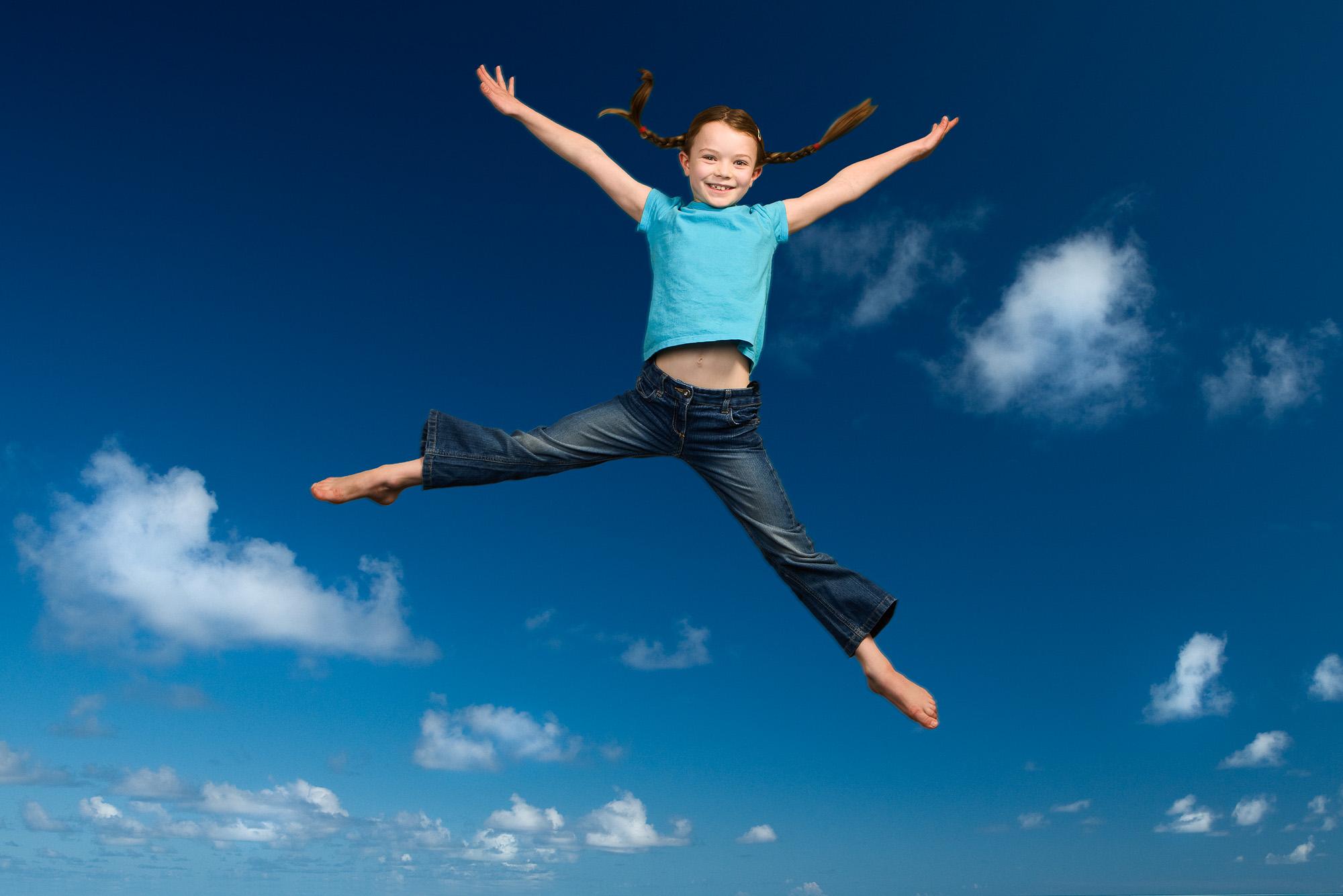 Tim Platt - Girl jumping with blue sky background