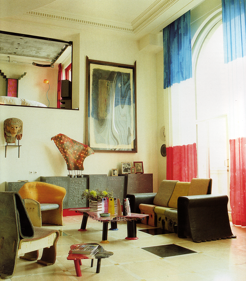 "ABOVE: ""All furniture in the apartment was designed by Gaetano Pesce. The chairs, made of resin and felt and bent by hand, were prototypes for Pesce's most recent furniture collection. Pesce used felt because ""it has existed throughout civilization."" The small table in the foreground is the prototype for Pesce's   Samsone   table, made by Cassina. The Egyptian head is from 500 B.C. The sideboard, faced with lead, and the light fixture are unique, designed by Pesce. The tricolor curtains are hand-painted by Rubin. The bedroom is visible through the back wall of the living room."" [2]"