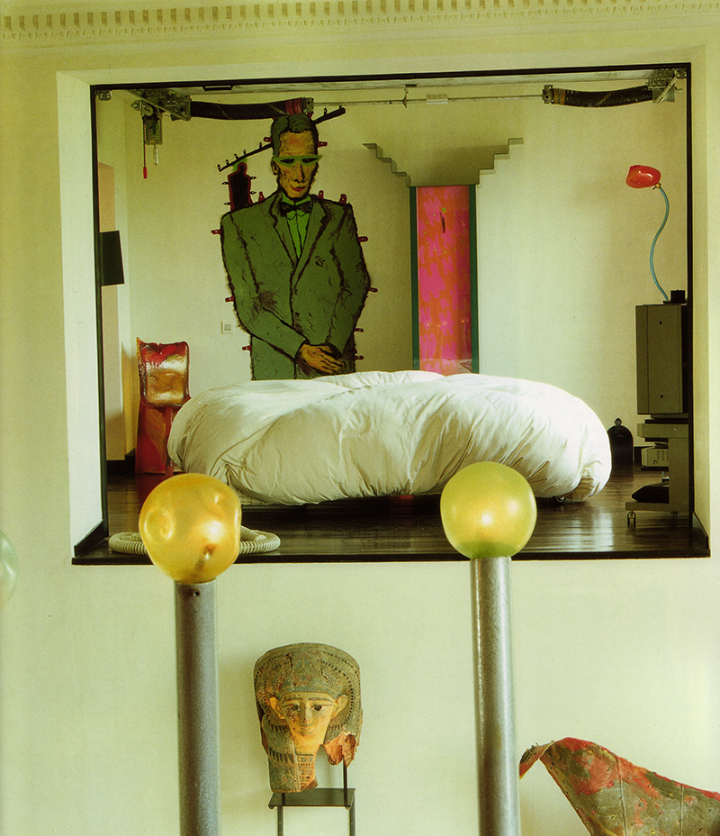 "ABOVE: The master bedroom, seen from the mezzanine, has a circular bed placed precariously close to the edge of the room. The room can be sealed from view by mechanized aluminum doors that work like the doors of a garage. The clock is unique, a prototype for a smaller version by George Sowden. The portrait of Rubin, made by Pesce, was created by drawing on a liquid material that is then allowed to solidify. Pesce describes the process as ""a fight with the material,"" because he must finish the drawing before it begins to harden."
