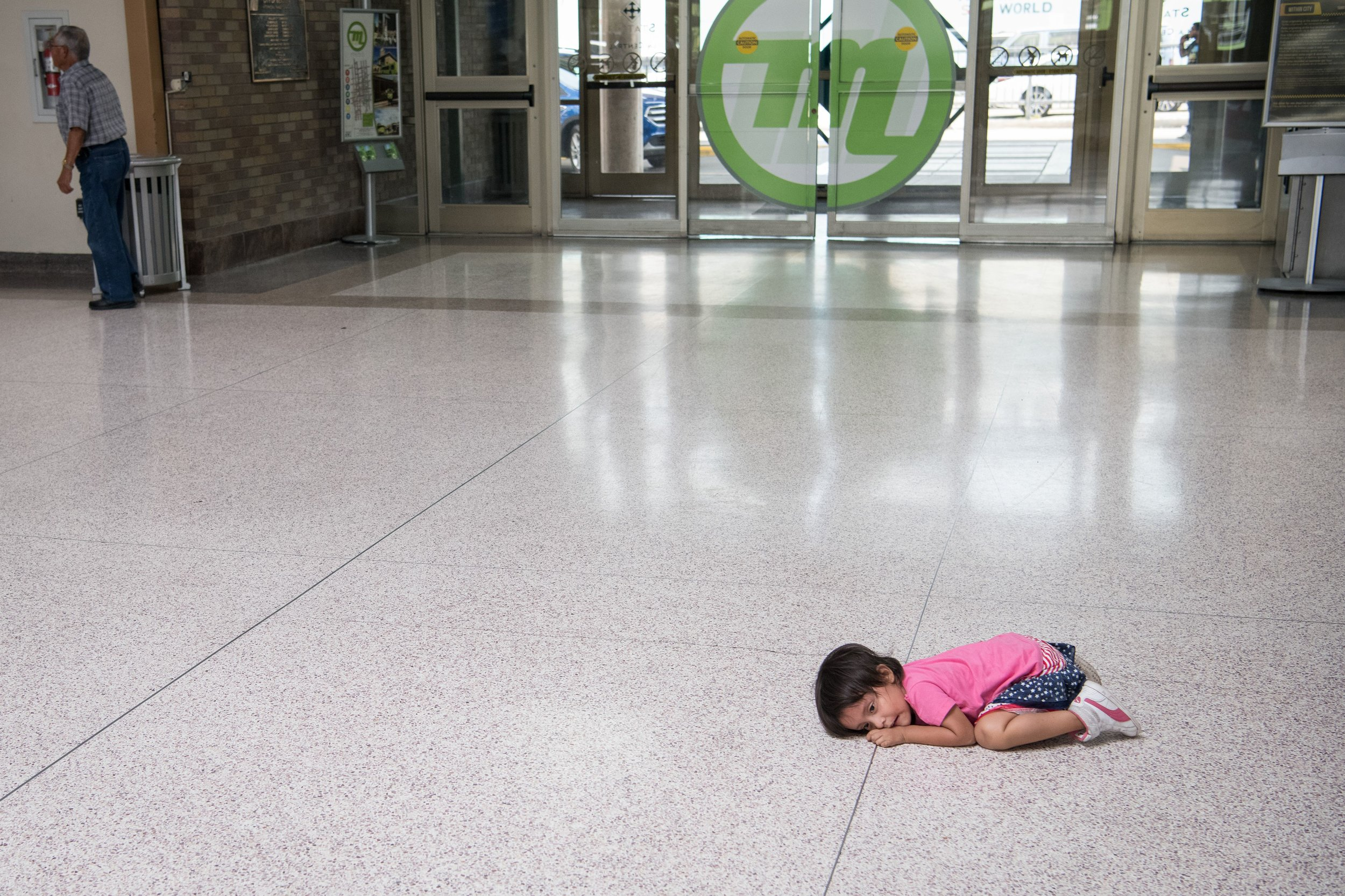 A young migrant girl sits on the floor as her father, recently released from federal detention with other Central American asylum seekers, gets a bus ticket at a bus depot on June 11, 2019, in McAllen, Texas. (Photo by LOREN ELLIOTT/AFP/Getty Images.)