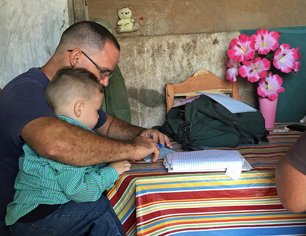 Father Juan Carlos with his son Jesus Alejandro examining records at the farm