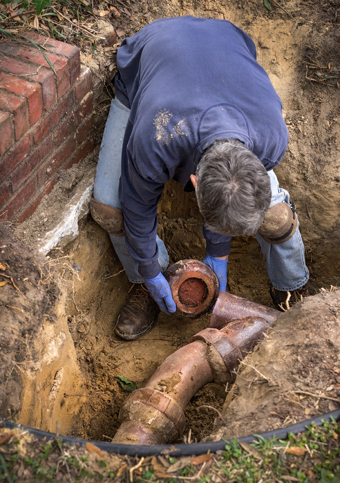 Image of a man working on a sewer pipe in the ground