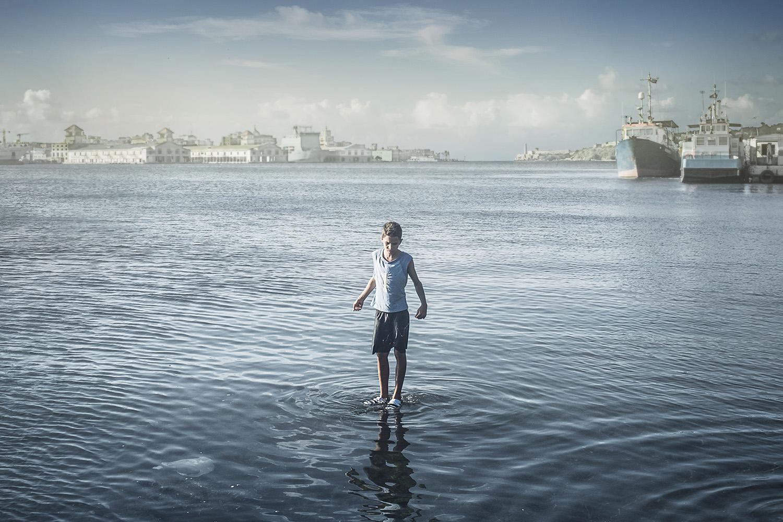 Kid fishing in Havana harbor