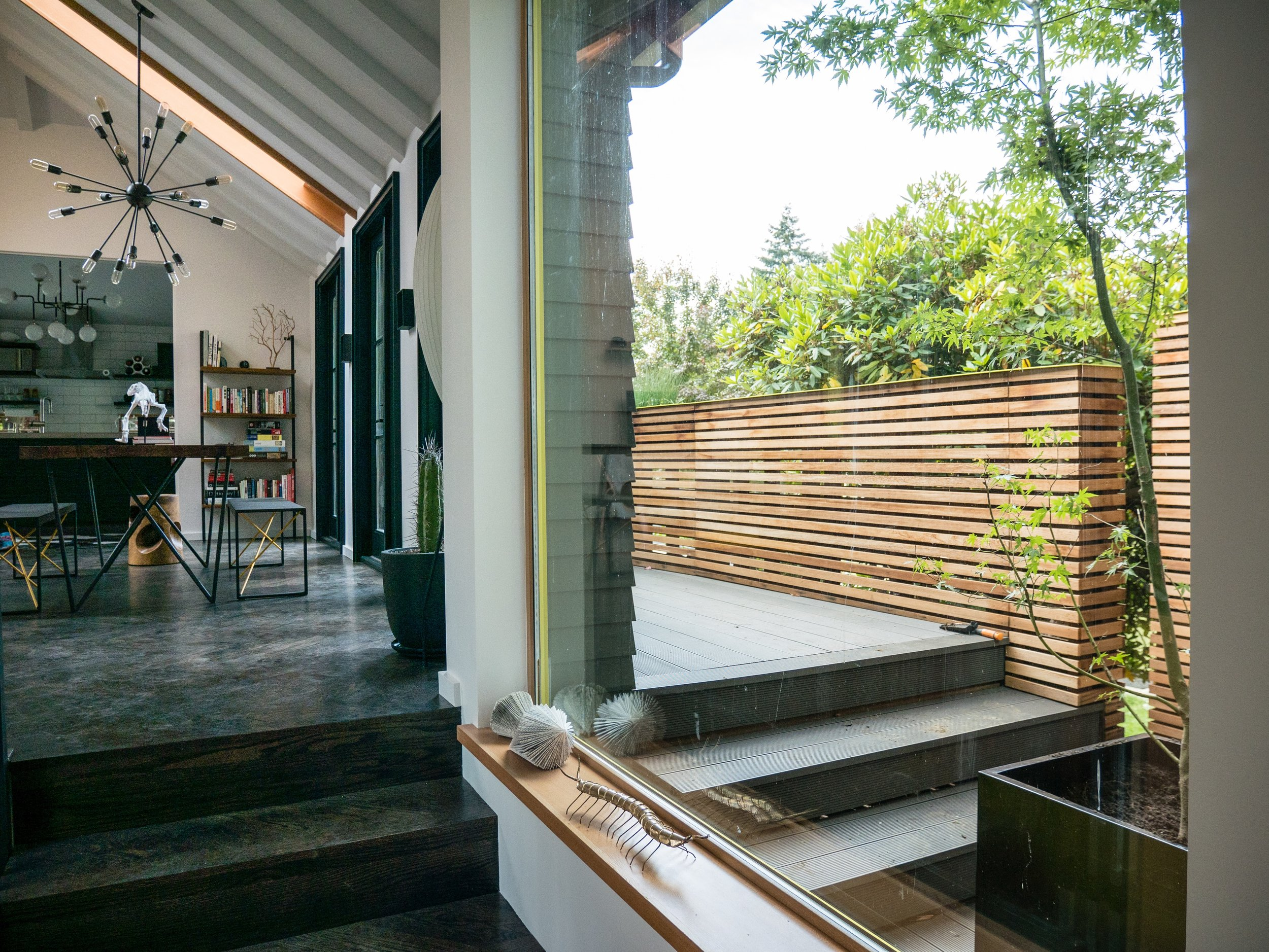 A slatted-wood planter wall frames the outdoor deck that runs along the house's west side.