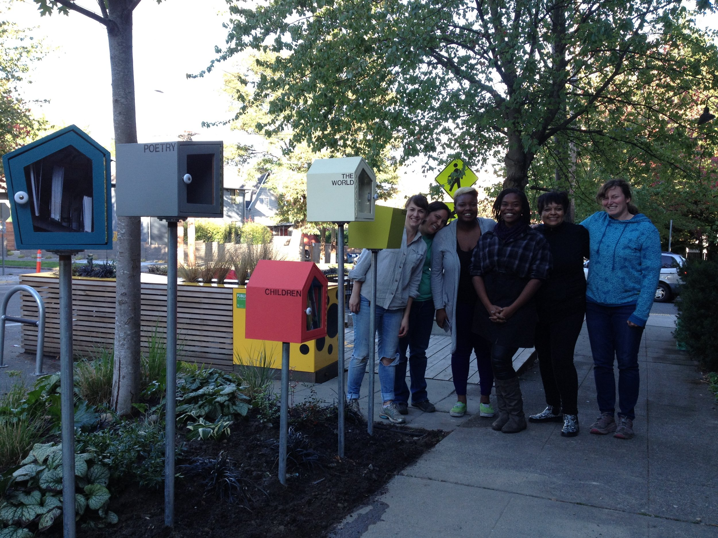 Parklet leaders smile beyond the library boxes.